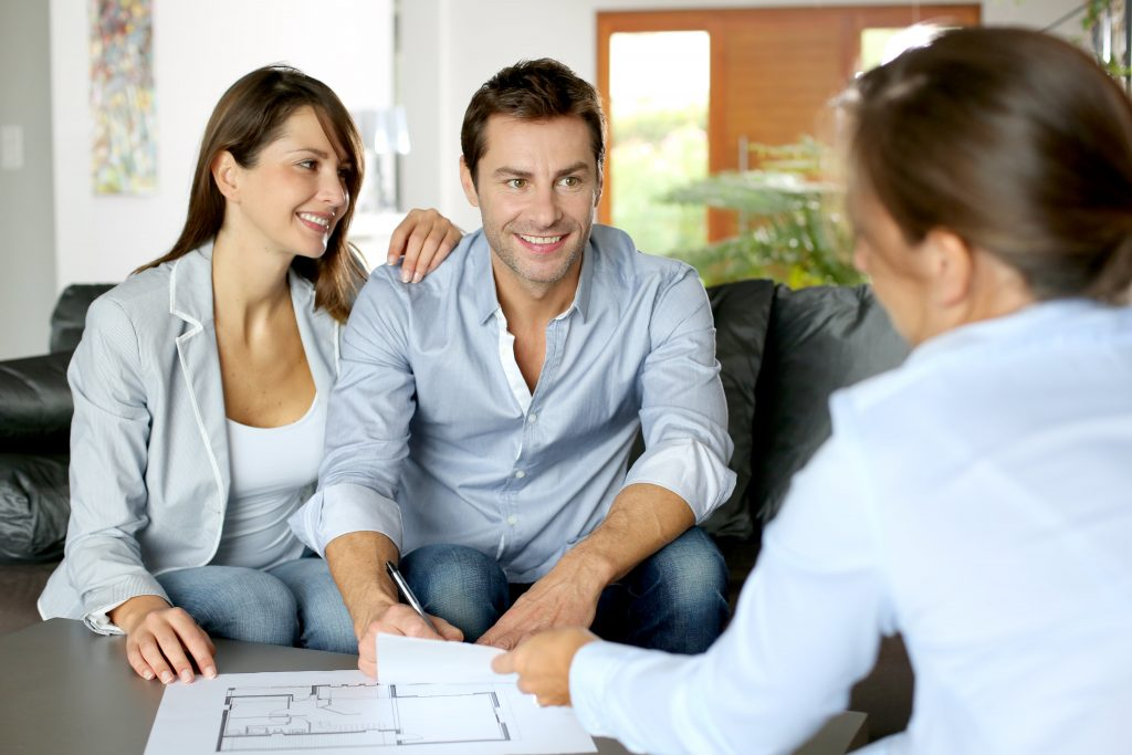 Home buyers looking over floor plans with Realtor.