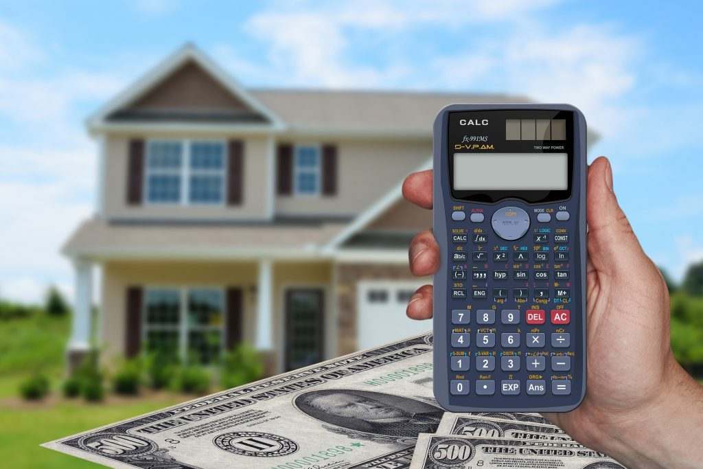 House in background with person holding calculator